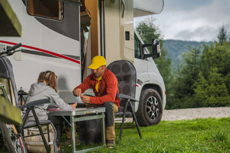 Caucasian Father with His Daughter Hanging Next to Modern Camper Van Class C Motorhome. Family RV Park Camping Theme.
