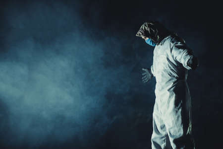 Caucasian Men Wearing Blue Mask and Hazmat Suit in Dark Smoky Place with Stretched Hands. Conceptual Photo.