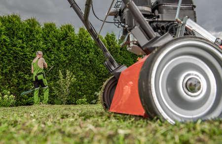 Backyard Garden Work with Lawn Aerator. Machine and Working Caucasian Gardener. Gardening Equipment. Imagens