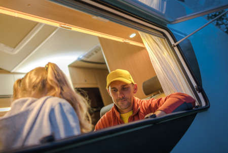 Caucasian Family Inside Camper Van. Father and His Daughter Seating Next to Open Wide RV Dinette Section Window. Class C Motorhome. Summer Recreational Vehicle Road Trip Theme. Imagens