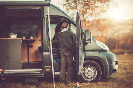 Caucasian Men in His 50s with Recreational Vehicle RV Class C Camper Van on a Camping. Travel and Van Life Theme.
