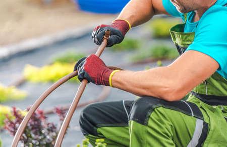 Caucasian Professional Gardener Attaching Plastic Pipeline Elements of Garden Irrigation System. Garden Technologies.