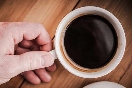 Fresh Brewed Black Arabica Coffee in White Coffee Cup. Caucasian Men Hand. Imagens