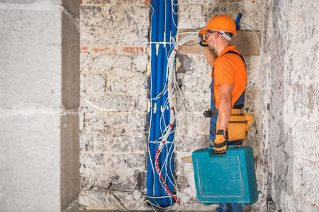 Professional Construction Contractor Worker in His 40s with Tools in His Hand Inside Concrete Blocks Built Building Interior. Construction Industry Theme.