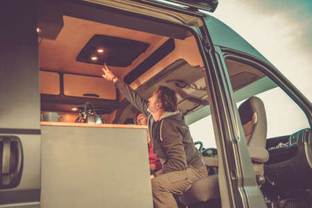 Caucasian Men Turning Off Camper Van Roof Mounted Air Condition Unit. RV Appliances. Caucasian Couple on a Camping.