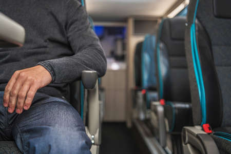Caucasian Passenger in His 40s Seating Inside Comfortable Coach Bus Close Up. Public Transportation Theme. Automotive Industry. Imagens