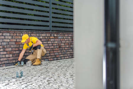 Caucasian Construction Worker Finishing Residential House Driveway Granite Pavement. Construction Industry Theme.