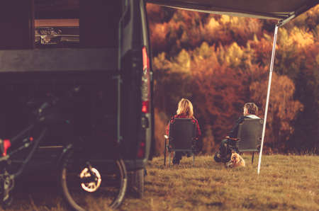 Scenic Fall Foliage RV Camper Camping. Caucasian Couple Seating Next to Their Motorhome and Enjoying the Scenery. Campsite Pitch. Imagens