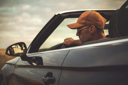 Caucasian Men in His 40s Wearing Baseball Cap Driving His Convertible Car with Roof Opened During Summer Road Trip. Automotive and Transportation Industry Theme. Cabrio Vehicle Drive.