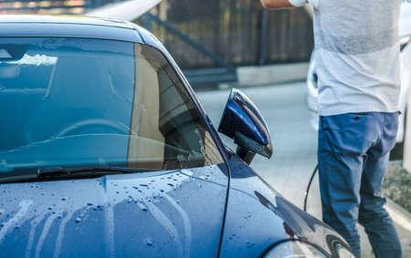 Caucasian Men Washing His Blue Sporty Looking Car on His Driveway. Car Pressure Washing.