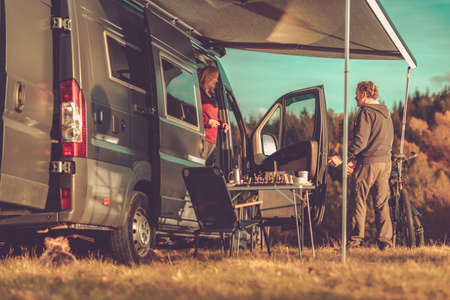 Caucasian Couple and Their Weekend Getaway. Camper Van RV Boondocking in Remote Place During Scenic Fall Foliage. Class B Motorhome RVing Theme.