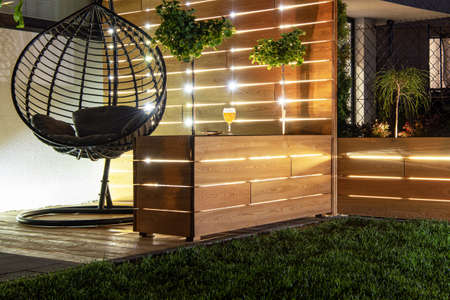 Residential Backyard Garden Wooden Recreation Place Deck with Table Illuminated by LED Outdoor Lighting. Custom Made Wooden Element.