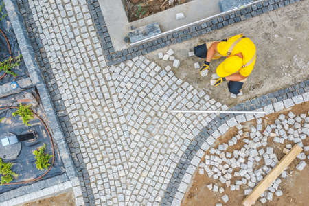 Caucasian Construction Worker in His 40s Paving Garden Path Aerial View. Garden Architecture Theme. Imagens