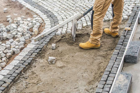 Construction Contractor Worker Paving Residential Path Using Granite Bricks.