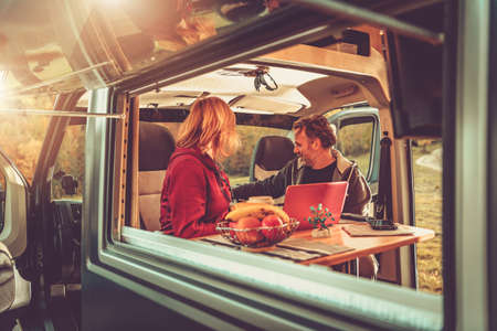 Caucasian Couple Inside Modern Camper Van During Their Wilderness Boondocking Vacation. Recreational Vehicle RV Theme.