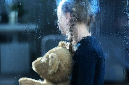Girl with Teddy Bear Behind Window Covered by Rain Drops. Children Depression and Social Issues Conceptual Photo.
