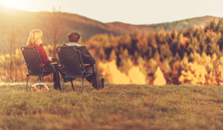Caucasian Couple Enjoying Outdoor Autumn Scenery Seating in the Middle of Nowhere with Their Dog. Fall Foliage Theme. 版權商用圖片