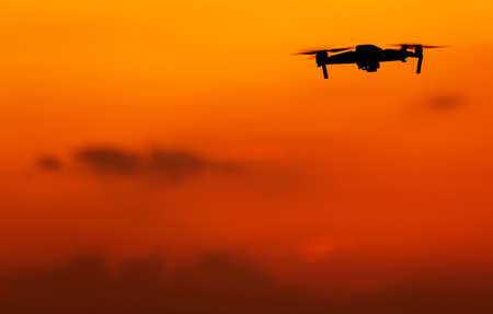 Modern Aerial Technologies. Unmanned Aerial Vehicle Drone on the Reddish Sunset Sky. Large Copy Space.