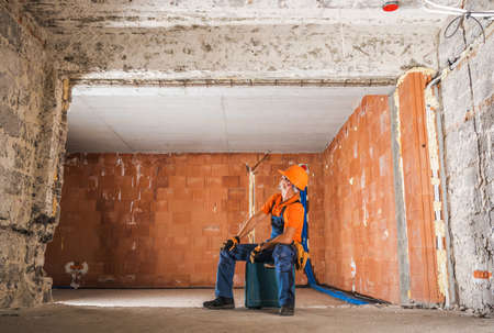 Caucasian Professional Construction Worker Inside Newly Rebuilt Building Interior. Raw Walls Around and the Worker Seating on His Power Equipment Case in the Middle of the Room. Stock fotó