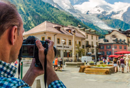Caucasian Tourist in His 60s with Digital Camera Taking Picture While on Vacation. City of Chamonix Mont Blanc, France.