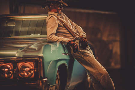 Thirty Seven Years Old Cowboy Wearing Leather Western Style Hat and Gloves and His Classic Vintage Car. Automotive Theme.