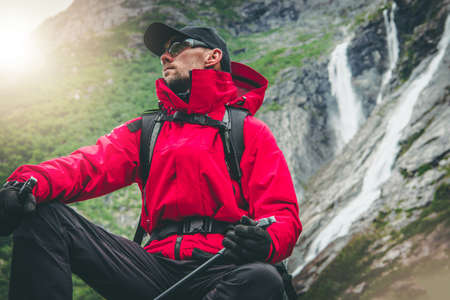 Outdoor Recreation. Active Caucasian Hiker Wearing Red Rainproof Jacket and Eyes Safety Glasses Seating Next to Scenic Alpine Waterfalls. Exploring the Trail.