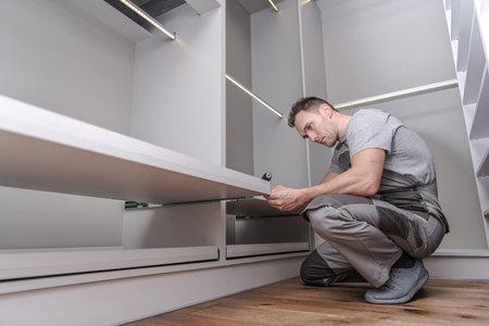 Caucasian Men in His 40s Assembling Elegant Modern White Closet Furnitures Inside His Apartment.