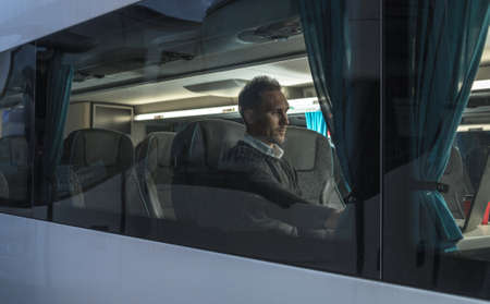 Caucasian Men Seating Inside Modern Bus in Premium Business Seat Section with Table. Coach Bus Transportation.