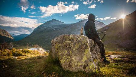 Male Alpine Hiker Taking Rest to Watch Scenic Sunset. Mountain Trail Recreation. Norwegian Landscape.
