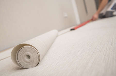 Roll of Modern Vinyl Wallpaper and Applying Preparation Inside Home Room.