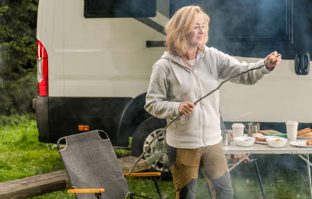 Caucasian Woman in Her 40s Having Fun on a Camping. Preparing Polish Sausage on Her Self Made Cooking Stick. Modern Class B Motorhome in Background. Reklamní fotografie