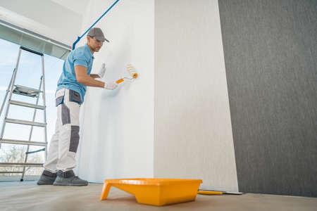 Caucasian Men in His 40s Applying Modern Canvas Textured Vinyl Wallpaper in the Apartment Room. Interior Renovation Theme. Reklamní fotografie