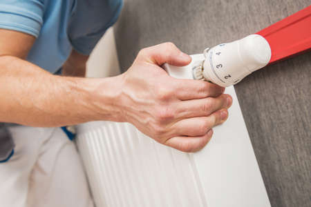 Caucasian Worker in His 40s Installing Heating Elements. Residential Heating Radiator Installation and Adjustment Close Up Photo. Reklamní fotografie