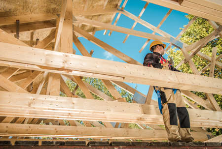 Skeleton Wood Frame Of House Building. Caucasian Contractor Worker on the Attic Frame. Industrial Theme.