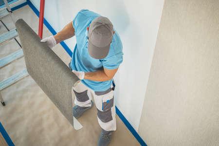 Home Interior Renovation. Caucasian Worker in His 40s Preparing Vinyl Wallpaper For Wall Applying. Industrial Theme. Reklamní fotografie