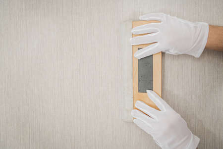 Worker with Clean White Gloves and Soft Wooden Vinyl Squeegee Smoothing Tool Using For Modern Vinyl Wallpaper Application. Reklamní fotografie
