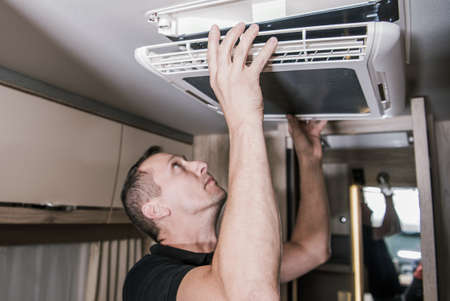 Caucasian RV Appliances Technician in His 40s at Work. Looking For Potential Issue with Air Condition Unit Inside Motorhome. RV Industry Theme.