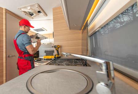 Recreational Vehicle RV Camper Appliances Caucasian Technician in His 40s Repair Air Condition Unit Inside Modern Travel Trailer.