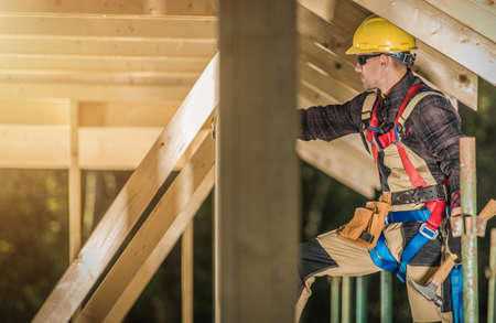Caucasian Construction Contractor in His 40s Wearing Safety Harness and Hard Hat. Wooden House Skeleton Frame Building. Industrial Theme.