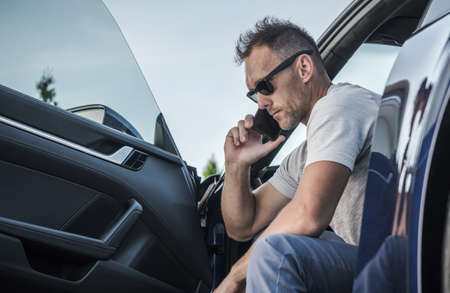 Caucasian Driver in His 40s Making Emergency Call From His Car. Calling Road Assistance. Transportation Industry Theme. Reklamní fotografie