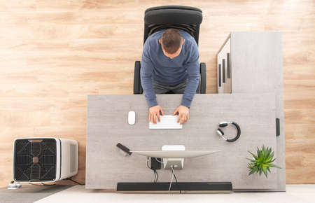 Online Home Office Worker in Front of Computer Top View. Caucasian Men in His 40s and His Workstation Inside His Home. Air Purifier Staying Next to His Workplace. Reklamní fotografie
