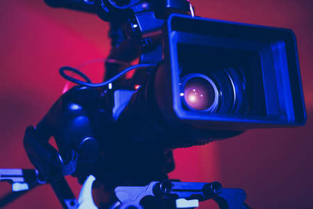 Modern Digital Cinema Camera with Moto Zoom Telephoto Lens Attached in Blue and Red Film Stage Illumination Close Up. Film Industry Equipment. Reklamní fotografie
