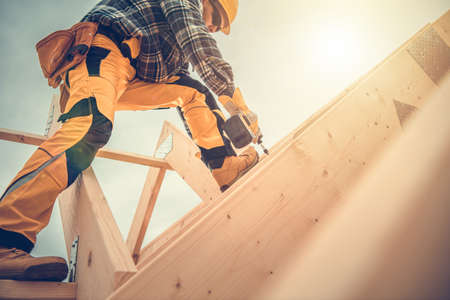 Caucasian Contractor Worker in His 40s with Drill Driver in His Hand. Carpenter Working on Wooden House Skeleton Frame Roof Section. Construction Industry Theme. Reklamní fotografie