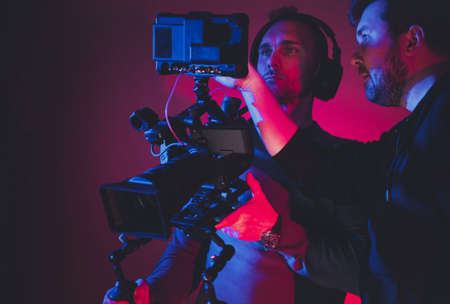 Two Caucasian Men Film Camera Crew Consulting Newly Taken Footage Reviewing on Large Digital Storage Display. Digital Videography Industry Theme. Reklamní fotografie