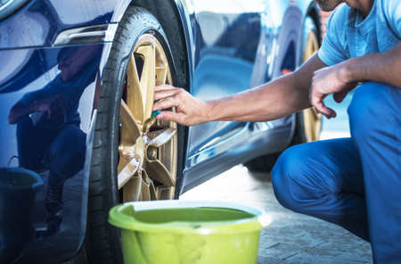 Caucasian Men Washing and Detailing His Exotic Car Alloy Wheels Close Up. Automotive Theme. Reklamní fotografie
