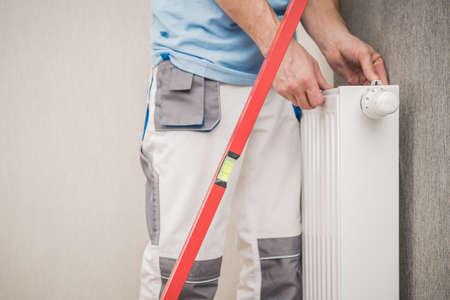 Caucasian Wall Heating Radiator Installer with Red Spirit Level. Residential Heating System Installation. Reklamní fotografie