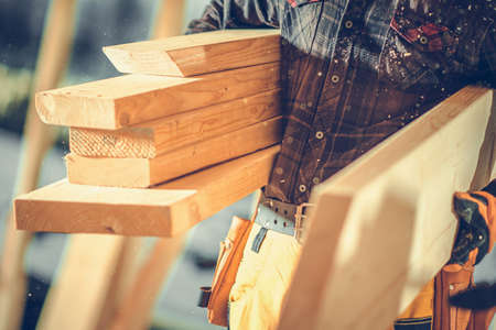 Construction Worker Moving Pieces of Wood Beams in Construction Zone. Close Up Photo. Industrial Theme. Reklamní fotografie
