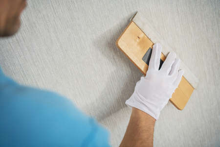 Canvas Textured Vinyl Wallpaper Installation with Squeegee Tool. Apartment Remodeling.