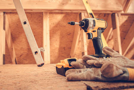 Drill driver and safety gloves inside wooden building construction site.