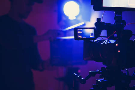 Documentary Film Stage in Blue Illumination. Professional Film Lighting and Digital Cinema Camera. Film Crew in Front of Camera with Movie Clapper in His Hands.